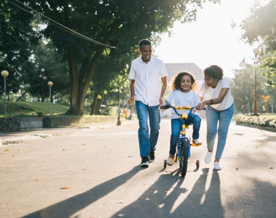 parents teaching child to ride bike