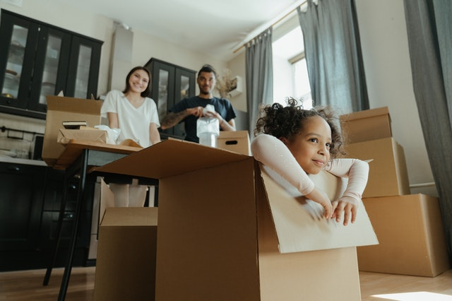Family unpacking boxes with children